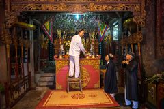 Hanoi, Vietnam - Jun 22, 2017: Oude mens die vereringsdienstenaanbod op altaar op vakantie in communaal huis voorbereiden bij zo  Royalty-vrije Stock Afbeelding