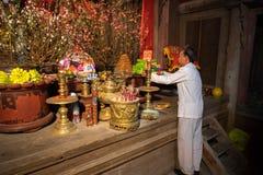 Hanoi, Vietnam - Jun 22, 2017: Oude mens die vereringsdienstenaanbod op altaar op vakantie in communaal huis voorbereiden bij zo  Royalty-vrije Stock Foto's