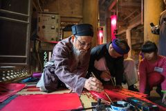 Hanoi, Vietnam - Jun 22, 2017: Scholar writes Chinese calligraphy characters in communal house at So village, Quoc Oai district. C. Alligraphy giving is a stock photography