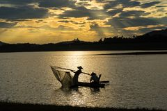 Hanoi, Vietnam - June 12, 2016: Mo lake with a couple of fishers catching fish by net trap in beautiful sunset period in Son stock photo