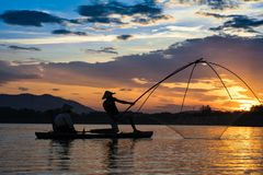 Hanoi, Vietnam - June 12, 2016: Dong Mo lake with a couple of fishers catching fish by net trap in beautiful sunset period in Son. Tay town, Hanoi, Vietnam Stock Photos