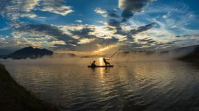 Hanoi, Vietnam - June 12, 2016: Dong Mo lake with a couple of fishers catching fish by net trap in beautiful sunset period in Son. Tay town, Hanoi, Vietnam. The Stock Images