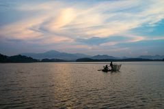 Hanoi, Vietnam - June 5, 2016: Lake scene at twilight with a couple of fishers catching fish by net trap on lake with smoke in Son. Tay county town Stock Image