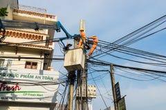 Hanoi, Vietnam - Juni 14, 2015: De arbeiders herstellen telecommunicatiekabel na zwaar windonweer in Truong Dinh-straat Royalty-vrije Stock Afbeeldingen