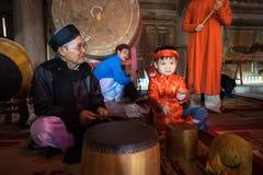 Hanoi Vietnam - Juni 22, 2017: Vietnamesisk gammal traditionell folk sångare med barn som lär att spela folk instrument i kollekt Arkivbilder