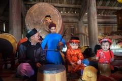 Hanoi Vietnam - Juni 22, 2017: Vietnamesisk gammal traditionell folk sångare med barn som lär att spela folk instrument i kollekt Arkivfoton