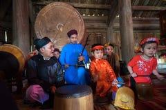 Hanoi Vietnam - Juni 22, 2017: Vietnamesisk gammal traditionell folk sångare med barn som lär att spela folk instrument i kollekt Royaltyfri Fotografi