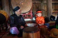 Hanoi Vietnam - Juni 22, 2017: Vietnamesisk gammal traditionell folk sångare med barn som lär att spela folk instrument i kollekt Arkivbild