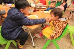 Hanoi, Vietnam - Maart 11, 2018: De mooie oudere broer voedt voor zijn jongere zuster in één markt royalty-vrije stock fotografie