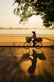 Hanoi Vietnam - 28 Maj, 2013: Gatuförsäljaren rider hennes cykel över solnedgången på den västra sjön Royaltyfri Foto