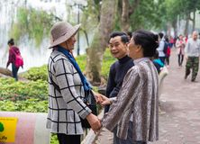 Hanoi, Vietnam - Mar 15, 2015: A couple happily seeing their friend at Hoan Kiem lake, Hoan Kiem district. The women holding hands Stock Images