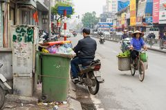 Hanoi, Vietnam - Mar 15, 2015: Wide view of Hanoi street focusing on rubbish bin. The word `No Littering` on the next old electr. Ical cabinet, and the woman Stock Image