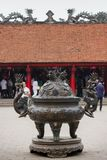 A Big antique bronze incense burner with tourist background in the House of Ceremonies at Temple of Literature Original built in. Hanoi, Vietnam - March 27,2018 Royalty Free Stock Photography