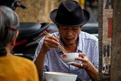 Street food lunch Hanoi. Hanoi, Vietnam - March 16, 2018: Local man having lunch on a street food stall in central Hanoi stock image