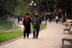 Hanoi Vietnam - 10 mars, 2012: Gamla par som tillsammans går runt om Hoan Kiem sjön Arkivfoton
