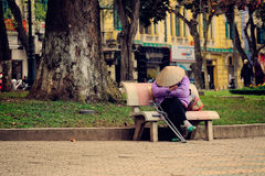 Hanoi Vietnam - 10 mars, 2012: Kvinnasömnen på bänken på Hoan Kiem sjön Royaltyfri Foto