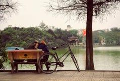 Hanoi Vietnam - 10 mars, 2012: Paren sitter på bänken bredvid deras cykel på Hoan Kiem sjön Arkivbild