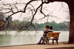 Hanoi Vietnam - 10 mars, 2012: Paren sitter på bänken på Hoan Kiem sjön Arkivbild