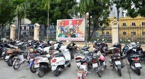 Hanoi Vietnam - Marz 1, 2015: Many scooters in front of propaganda billboards Royalty Free Stock Image