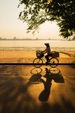 Hanoi, Vietnam - 28 May,2013: The street vendor ride her bicycle across the sunset at West lake Royalty Free Stock Photo