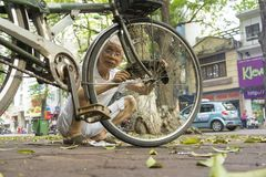 Hanoi, Vietnam - May 2, 2014: Unidentified old man fixing his bicycle on street side in Phan Dinh Phung str, Hanoi, Vietnam stock images