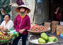 HANOI, VIETNAM - MAY 22, 2017: Woman selling tropical fruit on a. HANOI, VIETNAM - MAY 22, 2017: Woman selling tropical fruit from bicycle stalls on a busy Hanoi Royalty Free Stock Image