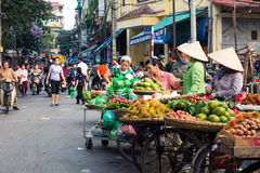 HANOI, VIETNAM - MAY 22, 2017: Woman selling tropical fruit on a. HANOI, VIETNAM - MAY 22, 2017: Woman selling tropical fruit from bicycle stalls on a busy Hanoi Royalty Free Stock Images