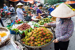 HANOI, VIETNAM - MAY 22, 2017: Woman selling tropical fruit on a. HANOI, VIETNAM - MAY 22, 2017: Woman selling tropical fruit from bicycle stalls on a busy Hanoi Stock Photo
