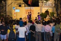 Hanoi, Vietnam - 2 Nov., 2014: De toerist let op een vrije show van oud volksmuziek en lied op Ma Mei straat, oud kwart van Hanoi Stock Afbeeldingen