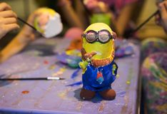 Hanoi, Vietnam - Nov 2, 2014: Minion, famous character from animation movie Despicable Me, made from plaster, and painted by child. Ren with color ink and brush royalty free stock photo