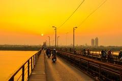 Hanoi Vietnam - 18 November, 2012: Folket går hem i solnedgången på den långa Bien bron Arkivfoto