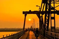 Hanoi Vietnam - 18 November, 2012: Folket går hem i solnedgången på den långa Bien bron Arkivbild