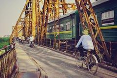 Hanoi Vietnam - 18 November, 2012: Folket och drevet går över den långa Bien bron Royaltyfri Bild