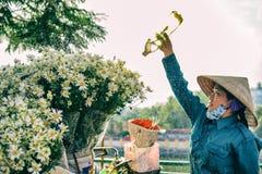 Hanoi, Vietnam: 24-Novemver, 2014: Het water van de bloemverkoper de bloemen in de straat Royalty-vrije Stock Afbeeldingen
