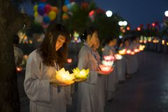 Hanoi, Vietnam - Oct 10, 2014: Buddhists hold flower garlands and colored lanterns for celebrating Buddha`s birthday organised at. Tran Quoc temple Royalty Free Stock Photos