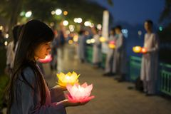 Hanoi, Vietnam - Oct 10, 2014: Buddhists hold flower garlands and colored lanterns for celebrating Buddha`s birthday organised at. Tran Quoc temple Stock Photo