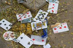 Hanoi, Vietnam - Oct 25, 2015: Old playing cards on a pile of garbage on street stock image