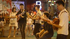 HANOI, VIETNAM - OCTOBER 13, 2016: Street performers with guitar, with audience in the background. stock footage