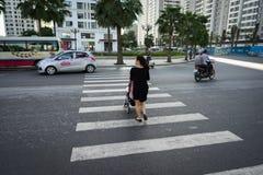 Hanoi Vietnam - Oktober 19, 2016: Moder med en behandla som ett barnsittvagn som korsar gatan i Minh Khai Medel som kör på gatan Arkivfoton