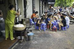 Hanoi, Vietnam - Sep 2, 2015: People eating Vietnamese traditional noodle soup Pho on sidewalk. Eating on pavement is common in Ha. Noi Royalty Free Stock Photography