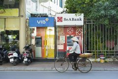 Hanoi, Vietnam - Sep 14, 2014: Unidentified woman cycles passing ATM on Le Dai Hanh street.  Stock Image