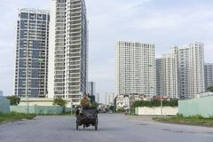 Hanoi, Vietnam - Sept 21, 2014: Unidentified woman cycling on outskirts street of Hanoi city, with high buildings on background.  Royalty Free Stock Photos