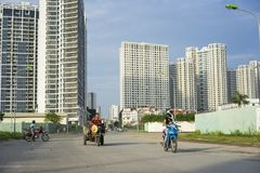 Hanoi, Vietnam - Sept 21, 2014: Unidentified woman cycling on outskirts street of Hanoi city, with high buildings on background.  Stock Images