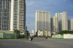 Hanoi, Vietnam - Sept 21, 2014: Unidentified woman cycling on outskirts street of Hanoi city, with high buildings on background.  Stock Photography