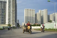 Hanoi, Vietnam - Sept 21, 2014: Unidentified woman cycling on outskirts street of Hanoi city, with high buildings on background.  Royalty Free Stock Photo