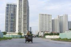 Hanoi, Vietnam - 21 settembre 2014: Donna non identificata che cicla sulla via di periferie della città di Hanoi, con le alte cos Fotografie Stock Libere da Diritti