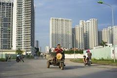 Hanoi, Vietnam - 21 settembre 2014: Donna non identificata che cicla sulla via di periferie della città di Hanoi, con le alte cos Fotografia Stock Libera da Diritti