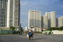 Hanoi, Vietnam - 21 settembre 2014: Donna non identificata che cicla sulla via di periferie della città di Hanoi, con le alte cos Immagini Stock