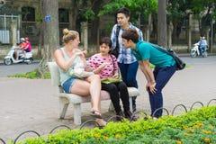 Hanoi, Vietname - 5 de abril de 2015: O grupo de estudantes aprende falar o inglês com os povos nativos ingleses do estrangeiro n Fotos de Stock Royalty Free
