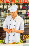 HANOI, VIETNAME - 16 DE DEZEMBRO DE 2016: Um cozinheiro corta um tomate em uma placa de corte vertical Foto de Stock